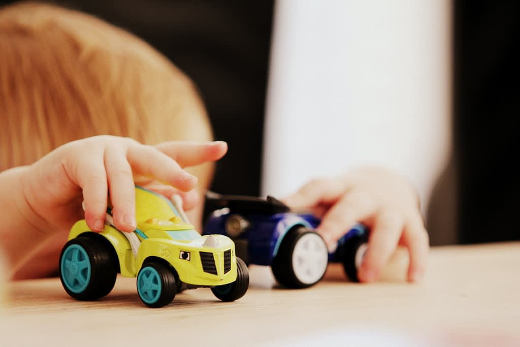 Toddler playing with toy cars
