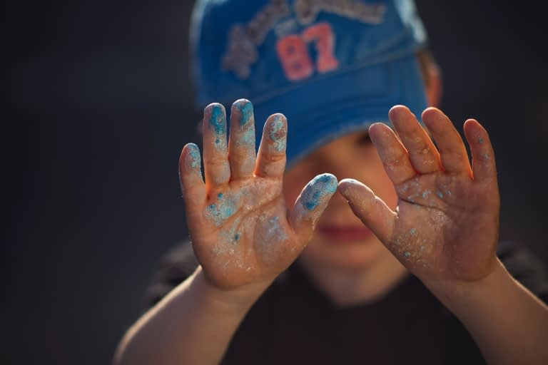 Childs hand covered in blue paint/chalk